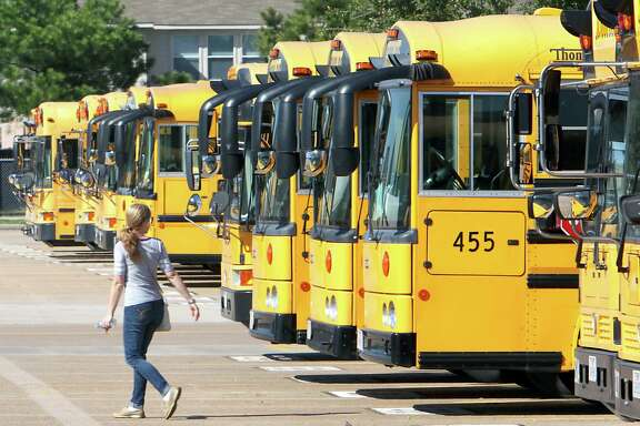 A school bus driver walks past a line of busses at a Katy Independent School District bus barn in 2014.     ( James Nielsen / Houston Chronicle )