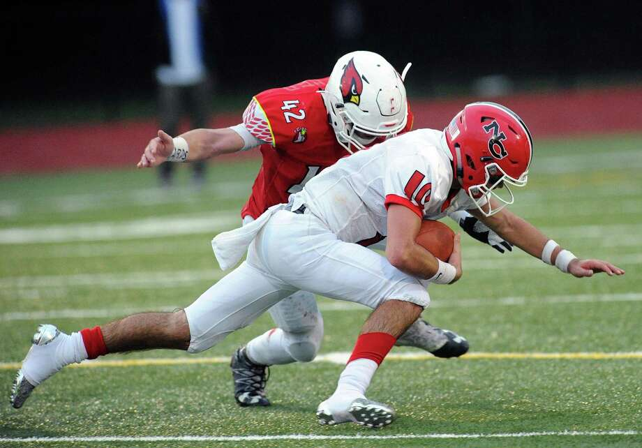 New Canaan quarterback Drew Pyne, foreground, is tackled by Gramoz Bici (#42) of Greenwich on a run at Greenwich on Saturday, Oct. 14. Photo: Bob Luckey Jr. / Hearst Connecticut Media / Greenwich Time
