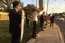 """About three dozen protesters gather Thursday night just outside the Barshop Jewish Community Center to protest the production of """"An Act of God."""""""