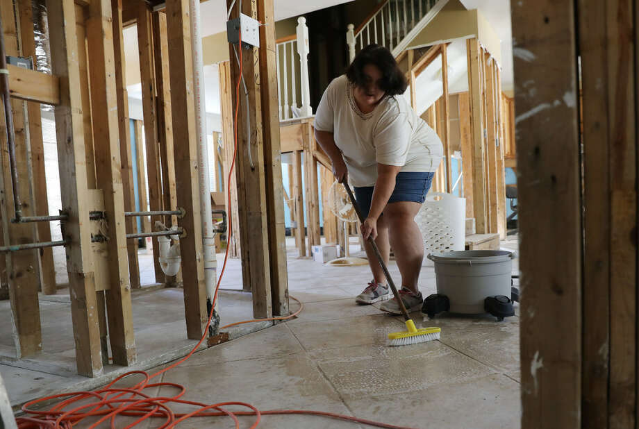 Cynthia Krueger scrubs with bleach in her flooded home after Harvey.