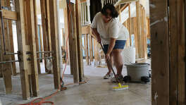 Cynthia Krueger scrubs a tile with bleach in her home that flooded as a result of Hurricane Harvey on Wednesday, Oct. 18, 2017, in Houston. (Elizabeth Conley / Houston Chronicle)