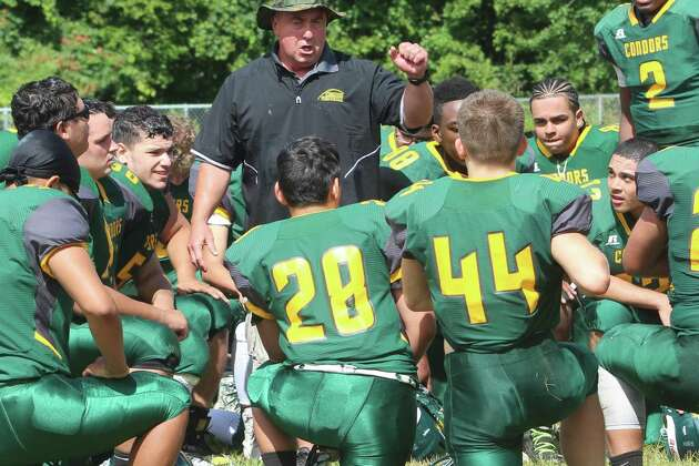 O'Brien Tech football coach Nick Aprea, middle, talks with his players following their victory over Abbott Tech/Immaculate in Ansonia Sept. 9, 2017.