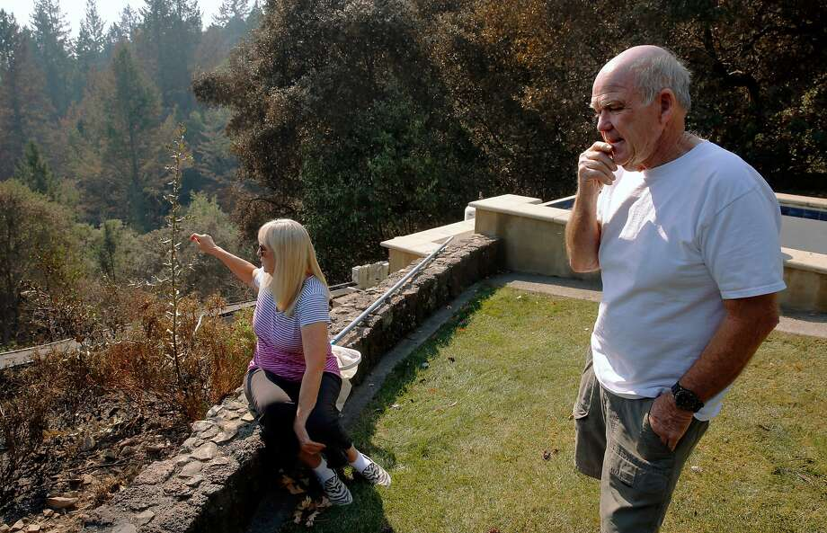 Jane and Steve Stone, at their home in Napa County, describe how the Partrick Fire came up from the canyon below as they evacuated the area. The fire spared their home. Photo: Michael Macor, The Chronicle