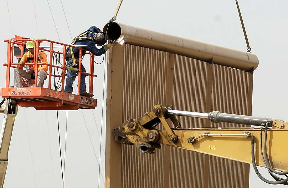 Crews work on a border wall model near Tijuana, Mexico. Companies are nearing an Oct. 26 deadline to finish building eight prototypes. Photo: Gregory Bull, Associated Press