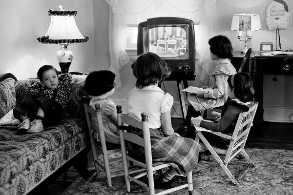 Children watch TV in 1953. Less-affluent youngsters spend more than three hours daily watching TV and media devices while kids in higher-income homes spend nearly two hours on such activities, a survey says.