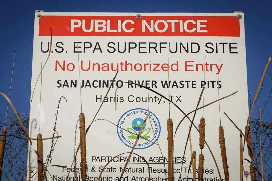 A sign warns the public about the EPA Superfund Site not to eat contaminated seafood caught from the water along I-10 near the San Jacinto River east of Houston, Tuesday, Dec. 17, 2013, in Channelview.  Texans Together, the Harris County Attorney's Office and residents are working together to spotlight the public health, fishing, and financial disaster that will result if a hurricane hits the San Jacinto Waste Pits, a highly vulnerable, toxic waste superfund site in the middle of the San Jacinto River and flows into Galveston Bay.  A recent government report reveals that the plastic lining placed in 2011 over the site's toxic wastes-- which the Waste Management and International Paper promised would protect the public for years, is eroding.  ( Michael Paulsen / Houston Chronicle ) Photo: Michael Paulsen, Staff / Internal