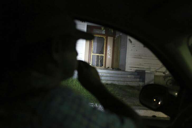 Ray Schultz checks out an empty house as he patrols the city's Westside, Wednesday, Oct. 11, 2017. Schultz and his wife, Tinker, started i-Watch-D5, a volunteer neighborhood watch group that patrols the streets of the San Antonio City Council District 5. Schultz was responding to a report from a citizen about possible drug houses. With a small video camera, he checks out conditions around the locations and reports them to the city for possible future improvements.
