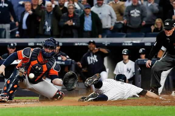Brett Gardner slides past Astros catcher Brian McCann, left, to score during the third inning of Wednesday's Game 5 at Yankee Stadium. The Yankees outscored the Astros 19-5 in three games in the Bronx after a pair of 2-1 Astros wins at Minute Maid Park.