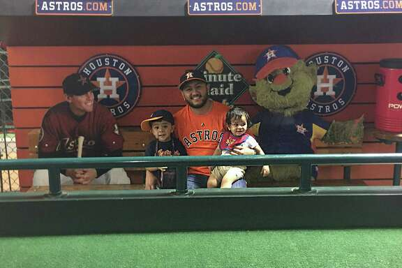 Flanked by cardboard cutouts of Astros great Craig Biggio and mascot Orbit, Victor Lombrana creates a memory with sons Leonardo, left, and Nicholas.