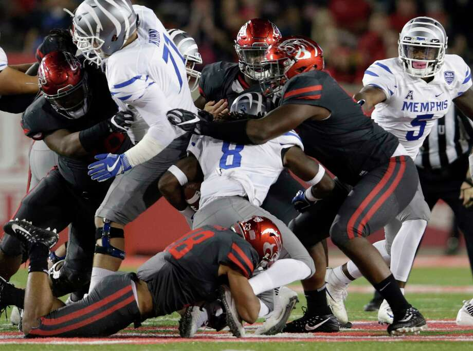 Memphis Tigers running back Darrell Henderson #8 is tackled by Houston Cougars cornerback Alexander Myers #18 and defensive end Nick Thurman #91 during the NCAA football game between the Memphis Tigers and the Houston Cougars at TDECU Stadium in Houston, TX on Thursday, October 19, 2017. Photo: For The Chronicle / Houston Chronicle