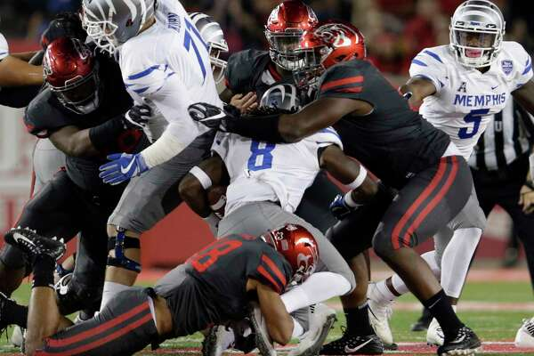 Memphis Tigers running back Darrell Henderson #8 is tackled by Houston Cougars cornerback Alexander Myers #18 and defensive end Nick Thurman #91 during the NCAA football game between the Memphis Tigers and the Houston Cougars at TDECU Stadium in Houston, TX on Thursday, October 19, 2017.