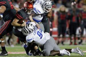 Houston Cougars quarterback Kyle Postma #3 scrambles and is tackled by Memphis Tigers defensive lineman Freddie Dillard #94 in the second quarter during the NCAA football game between the Memphis Tigers and the Houston Cougars at TDECU Stadium in Houston, TX on Thursday, October 19, 2017.