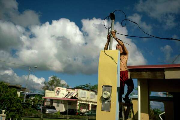 In this Friday, Oct. 13, 2017 photo, a resident tries to connect electrical lines downed by Hurricane Maria in preparation for when electricity is restored in Toa Baja, Puerto Rico. A month after the storm rolled across the center of Puerto Rico, power is still out for the vast majority.