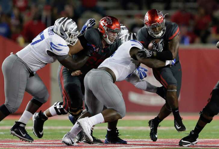 UH running back Duke Catalon, right, runs into Memphis's Jonathan Wilson in the first quarter Thursday night. Catalon finished with a career-best three rushing touchdowns.