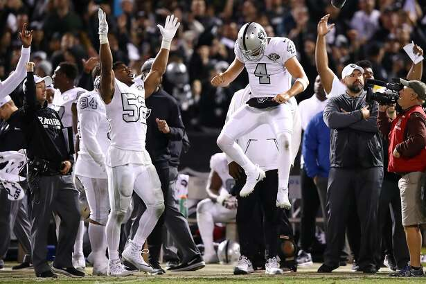 OAKLAND, CA - OCTOBER 19:  Khalil Mack #52 and Derek Carr #4 of the Oakland Raiders celebrate after the Michael Crabtree #15 touchdown is confirmed by officials to tie their game 30-30 with the Kansas City Chiefs with no time left on the clock at Oakland-Alameda County Coliseum on October 19, 2017 in Oakland, California.  (Photo by Ezra Shaw/Getty Images)
