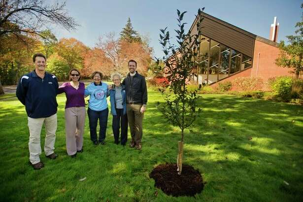 From left, Mike Reder with Reder Landscaping; Carol Sullivan, ministry coordinator with St. John's Episcopal Church; Carole Adams and Faye Ebach, anniversary committee co-chairs with St. John's Episcopal Church, and The Rev. Ken Hitch pose for a photo next to a crabapple tree they planted in celebration of the church's 150th anniversary in Midland. (Katy Kildee/kkildee@mdn.net)