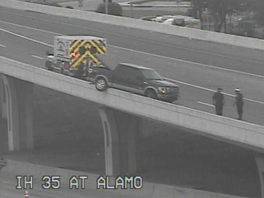 Authorities are responding to a pickup truck that's dangling over an Interstate 35 bridge near downtown. Photo: TxDOT