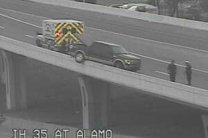 Authorities are responding to a pickup truck that's dangling over an Interstate 35 bridge near downtown.