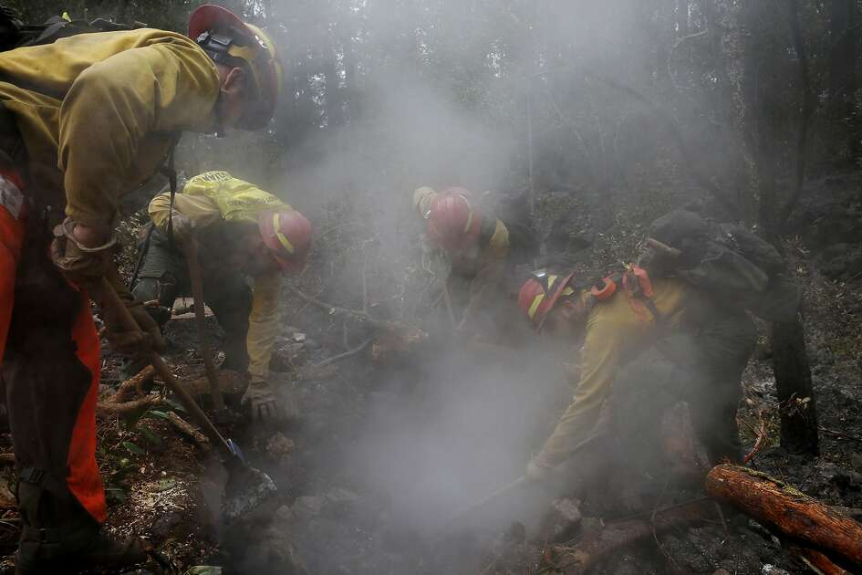 Firefighters from Eugene, Oregon, from left, Cameron McConnell, David Lopez-Parker, Skylar Lillingston and John Peterson work on mop up near Sugarloaf Ridge State Park Oct. 19, 2017 in Kenwood, Calif.