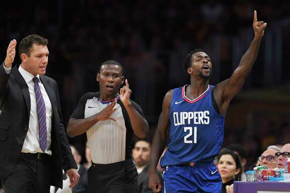 Los Angeles Clippers guard Patrick Beverley, right, celebrates a turnover as Los Angeles Lakers coach Luke Walton, left, talks to a referee during the first half of an NBA basketball game, Thursday, Oct. 19, 2017, in Los Angeles. (AP Photo/Mark J. Terrill)