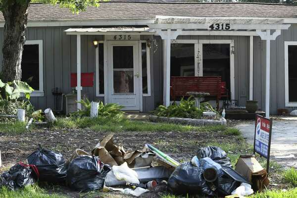 Discarded household materials are set on the yard of a house in  Bellaire in Houston. The neighborhood was damaged by Hurricane Harvey flood. On Friday, the National Association of Realtors reported home sales in Houston rose 4 percent from a year ago after plunging 25 percent in August. Lawrence Yun, chief economist for the realtors' group, said some of that gain may reflect investors purchasing damaged properties.