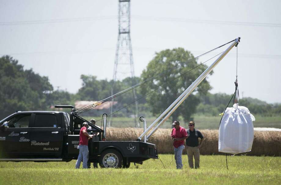 The day after, a crew hoists a bag holding the remains of a hot air balloon that crashed July 30, 2016 onto a waiting truck at the scene near Lockhart, Texas. Sixteen people were killed in the incident. Photo: Deborah Cannon /Associated Press / Austin American-Statesman