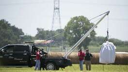 The day after, a crew hoists a bag holding the remains of a hot air balloon that crashed July 30, 2016 onto a waiting truck at the scene near Lockhart, Texas. Sixteen people were killed in the incident.