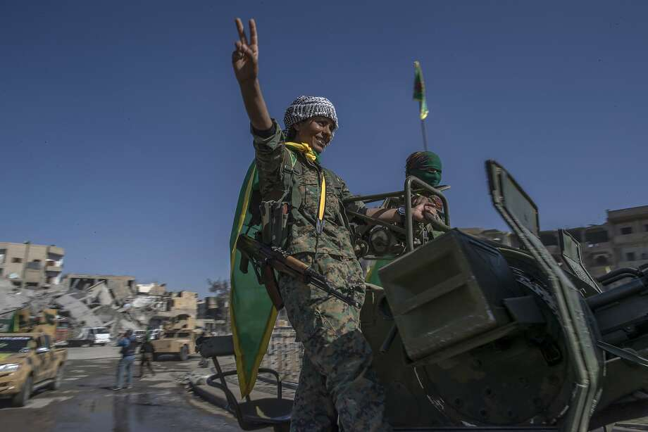 Fighters from the Kurdish female militia celebrate the military victory over the Islamic State at a main square in the northern Syrian city of Raqqa. Photo: Gabriel Chaim, Associated Press