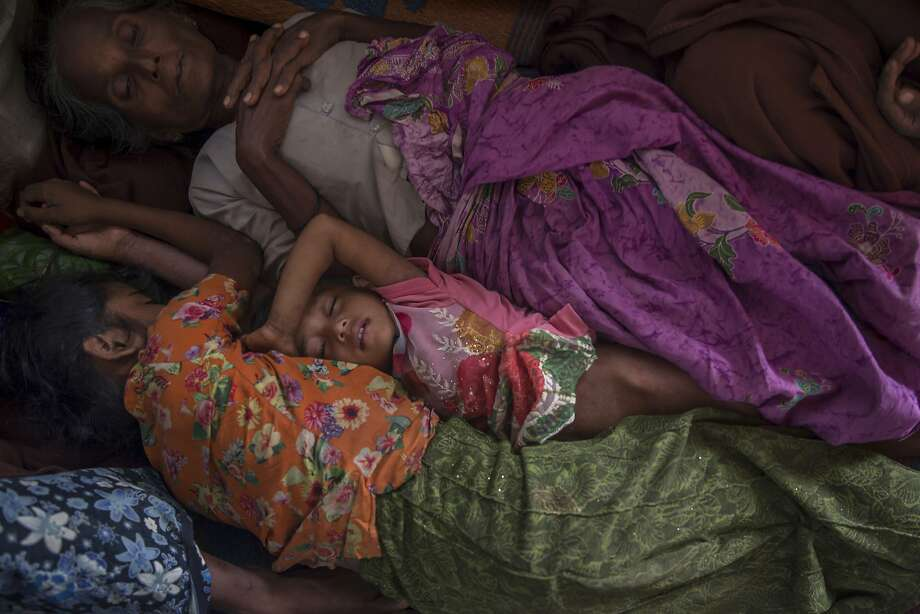 "A Rohingya Muslim girl Asma Bibi, center, sleeps between her grandmother and sister in a dormitory of a school as they wait for their family to be registered as refugees after which they will be allowed to proceed to build a shelter in Kutupalong refugee camp, Bangladesh, Friday, Oct. 20, 2017. UNICEF says the children who make up most of the nearly 600,000 Rohingya Muslims who have fled violence in Myanmar are seeing a ""hell on earth"" in overcrowded, muddy and squalid refugee camps in neighboring Bangladesh. (AP Photo/Dar Yasin) Photo: Dar Yasin, Associated Press"