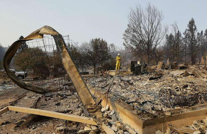 Cal Fire forester Kim Sone inspects damage at homes destroyed by fires in Santa Rosa, Calif., Thursday, Oct. 12, 2017. (AP Photo/Jeff Chiu)
