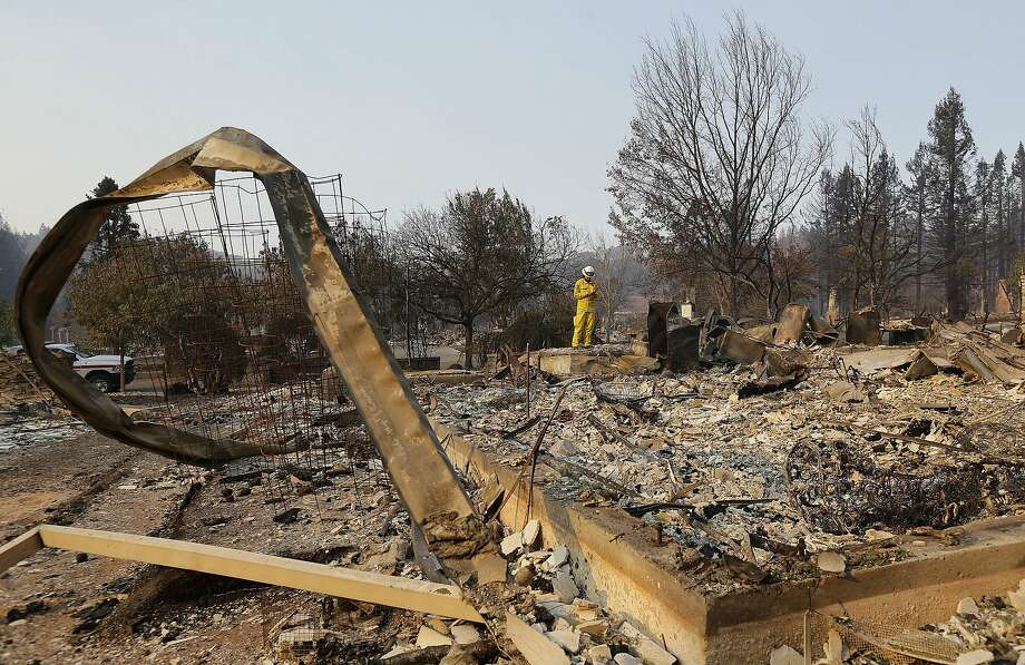 Kim Sone  of Cal Fire inspects damage  at homes destroyed by fires in Santa Rosa. PG&E has been ordered to preserve all evidence that may be linked to  the Wine Country blazes. Photo: Jeff Chiu, Associated Press