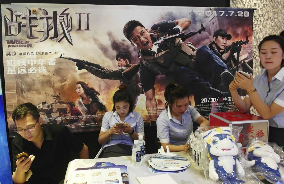"""In this Aug. 20, 2017, photo, cinema workers wait for customers in front of a poster for the movie """"Wolf Warriors II"""" in Yichang in central China's Hubei province. In this summer's """"Wolf Warrior II,"""" Chinese action star Wu Jing portrays a tough super-patriot who rescues both fellow countrymen and oppressed Africans with help from the People's Liberation Army and became China's biggest-grossing movie ever. This red-blooded nationalism has been channeled skillfully by President and ruling Communist Party leader Xi Jinping as he seeks to strengthen the party's role in Chinese life and shepherd the country's rise to prominence at a time when the United States and others in the West are seen to be in retreat. (Chinatopix via AP) Photo: Associated Press"""