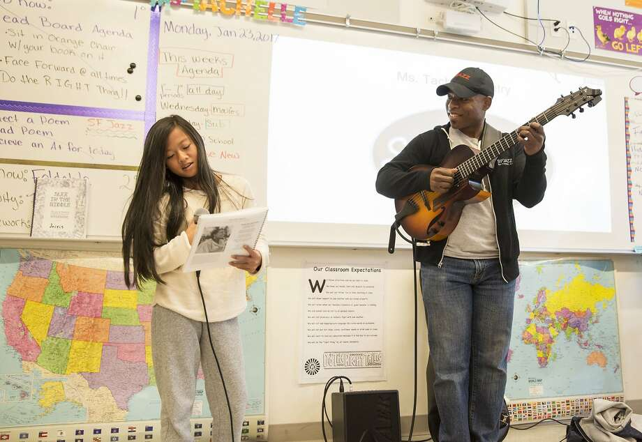 A student reads poetry, accompanied by jazz guitarist Terrence Brewer, in SFJazz's expanding Jazz in the Middle program at Willie L. Brown Jr. Middle School in San Francisco. Photo: Scott Chernis, SFJAZZ