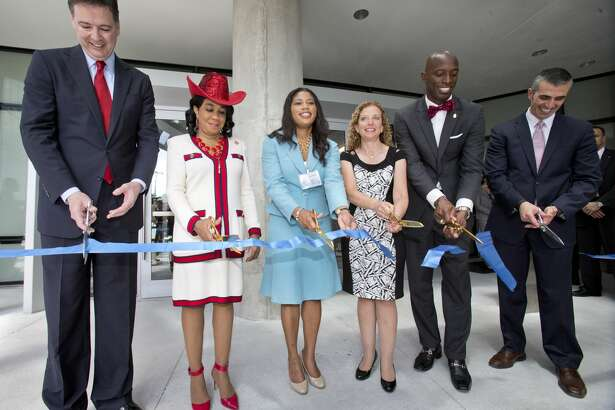 Dignitaries cut a ribbon to mark the dedication of the Federal Bureau of Investigation's new $194 million South Florida field office, Friday, April 10, 2015, in Miramar, Fla. The office is named for agents Benjamin P. Grogan and Jerry L. Dove, who were killed in an April 11, 1986, shootout with heavily armed bank robbers south of Miami. Five other FBI agents were wounded in what remains the bureau's bloodiest single day. Three survivors attended Friday's ceremony. From left, FBI Director James Comey, U.S. Rep. Frederica Wilson, acting GSA Administrator Denise Roth, U.S. Rep. Debbie Wasserman Schultz, Miramar, Fla. Mayor Wayne Messam, and George Piro, Special Agent in Charge, FBI Miami. (AP Photo/Wilfredo Lee, Pool)