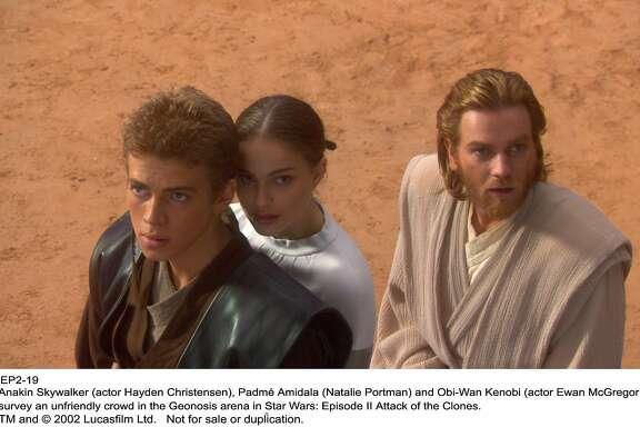 "Anakin Skywalker (Hayden Christensen), Padme Amidala (Natalie Portman) and Obi-Wan Kenobi (Ewan McGregor) survey an unfriendly crowd in the Geonosis arena in ""Star Wars: Episode II Attack of the Clones"""