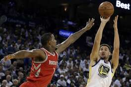 Golden State Warriors' Klay Thompson, right, shoots against Houston Rockets' Trevor Ariza during the second half of an NBA basketball game Tuesday, Oct. 17, 2017, in Oakland, Calif. The Rockets won 122-121. (AP Photo/Ben Margot)