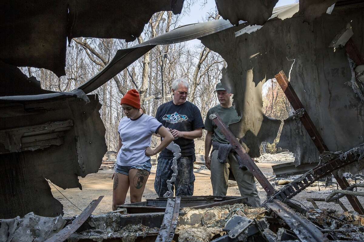 From left: Maryanne Garcia, Roland Tembo Hendel and Stephen Gray check on the remains of their neighbors mobile home at Franz Valley Road during the Sonoma County fires on Wednesday, Oct. 18, 2017, in Santa Rosa, Calif.