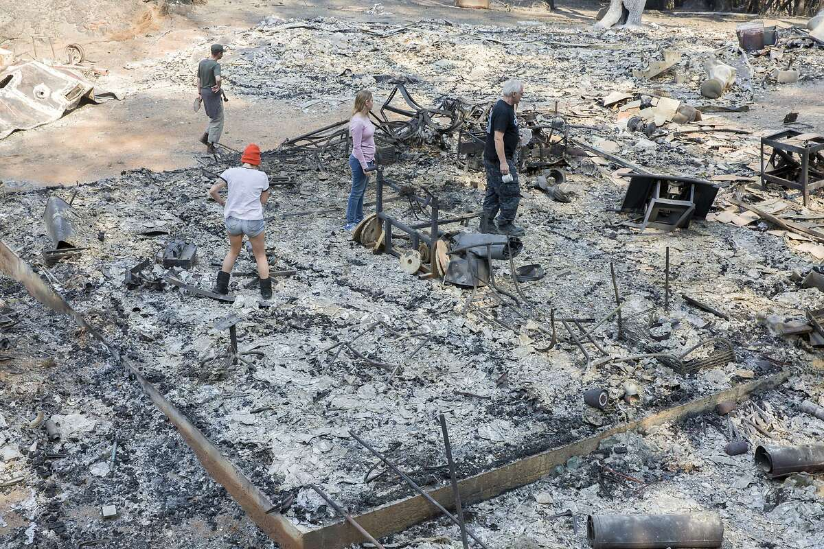 Roland Tembo Hendel (right) with friend and family check out the remains of Hendel's shared space destroyed by the Sonoma County fires at Franz Valley Road on Wednesday, Oct. 18, 2017, in Santa Rosa, Calif.