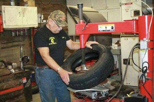 Ron Szymarek works in his business, Old Guy Tire Service. (Rich Harp/For the Tribune)