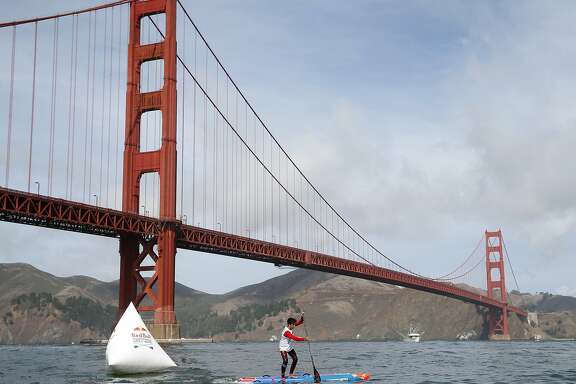 Second place winner Ryan Funk passes the final race buoy near the Golden Gate Bridge in the Red Bull Heavy Water stand-up paddleboard race in San Francisco, Calif. on Friday Oct. 20, 2017. Competitors began the course in the heavy surf off Ocean Beach and paddled through the Golden Gate to the finish line near the St. Francis Yacht Club.