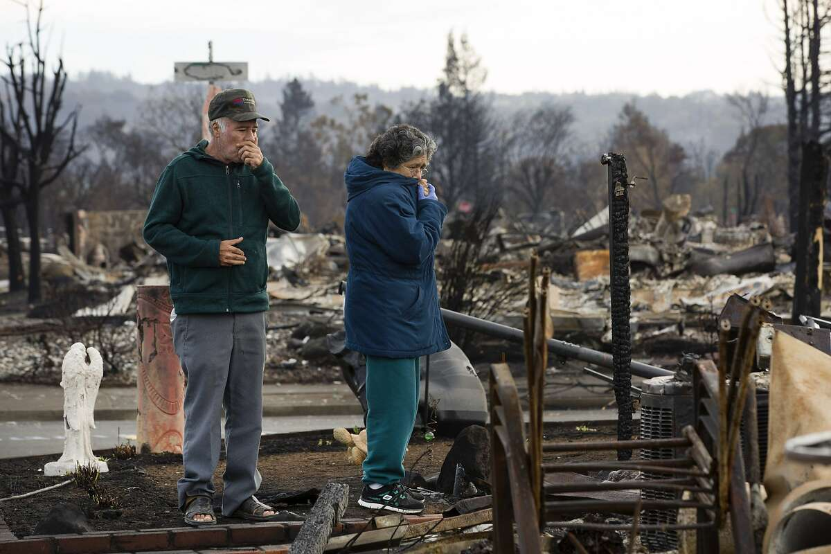 From left: Benjamin Hernandez and his wife Maria Guadalupe Hernandez take a moment to stare at their destroyed home in the Coffey Park neighborhood on Friday, Oct. 20, 2017, in Santa Rosa, Calif. Residents of the neighborhood were let back in for the first time since the Sonoma County fires to sift through what's left.