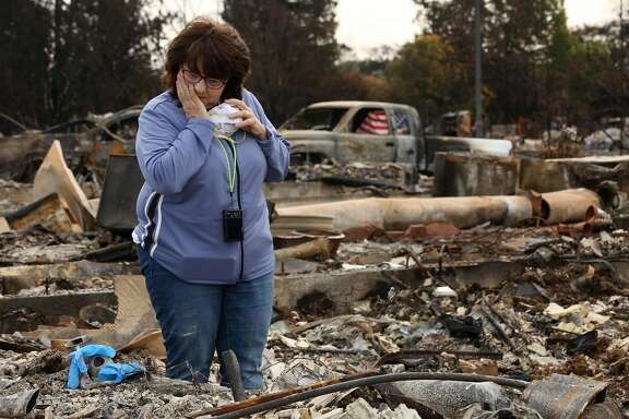 Donna Pittman takes a moment to herself as she's in the middle of her destroyed home in the Coffey Park neighborhood on Friday, Oct. 20, 2017, in Santa Rosa, Calif. Residents of the neighborhood were let back in for the first time since the Sonoma County fires to sift through what�s left.
