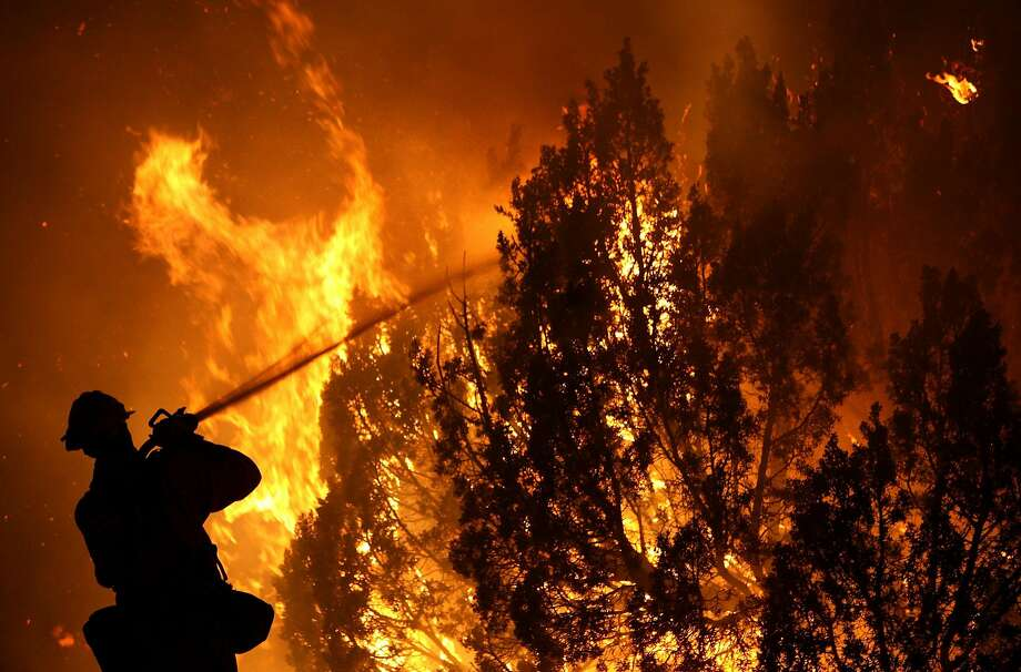 A Los Angeles County firefighter sprays water on burning trees as he fights the Station Fire on Aug. 30, 2009, in Acton. Photo: Justin Sullivan, Getty Images
