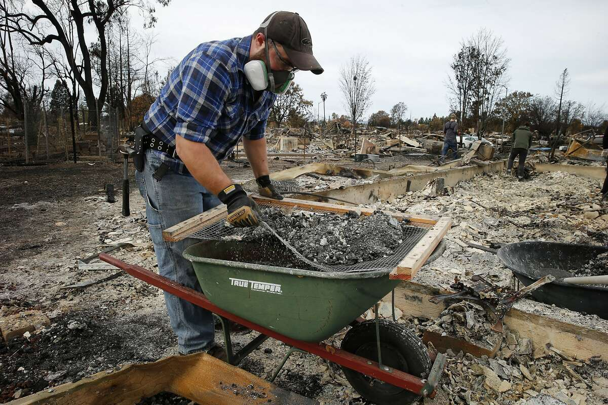Kenny Crain helps sort through the rubble for her sister Melissa Geissinger's belongings in the Coffey Park neighborhood on Friday, Oct. 20, 2017, in Santa Rosa, Calif. Residents of the neighborhood were let back in for the first time since the Sonoma County fires to sift through what�s left.
