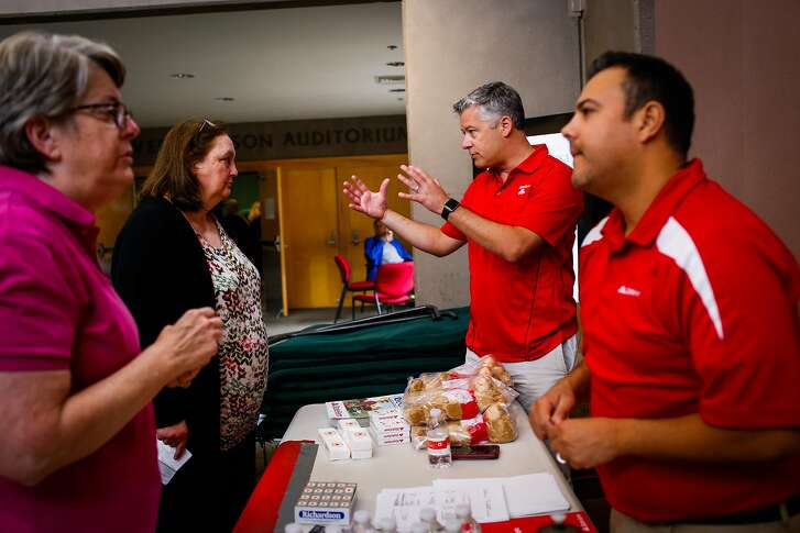 State farm representatives Ethan Cline (center) and Eddie Sandoval (right) speak with residents of Santa Rosa (left, declined to give anems0 at a Red Cross makeshift evacuation center at the Finley Community Center in Santa Rosa, Calif., on Tuesday, Oct. 10, 2017.