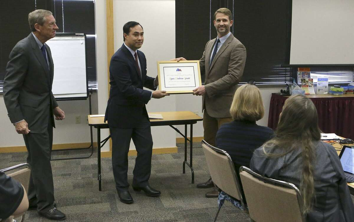 Ryan Sprott (right) receives the James F. Veninga Outstanding Teaching of the Humanities Award at a workshop session for teachers being held at the Education Service Center Region 20 Conference Center. Attended by U.S. Congressman Joaquin Castro (center), the award ceremony was held to recognize Sprott who received the highest rating from a panel of judges. Sprott teaches at the International School of ther Americas, a magnet program at NEISD's Lee High School. On the left is Michael L. Gillette, Executive Director for Humanities Texas. Sprott also received a check for $5,000 for earning the award.