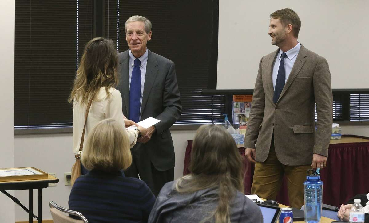 Ryan Sprott (right) smiles while his wife Erin Sprott (standing,holding envelope, facing away) is handed a check for $5,000 after her husband received the James F. Veninga Outstanding Teaching of the Humanities Award at a workshop session for teachers being held at the Education Service Center Region 20 Conference Center. Attended by U.S. Congressman Joaquin Castro (not pictured), the award ceremony was held to recognize Sprott who received the highest rating from a panel of judges. Sprott teaches at the International School of ther Americas, a magnet program at NEISD's Lee High School. Handing the check to Erin Sprott is Michael L. Gillette (center), Executive Director for Humanities Texas.