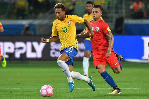 Neymar escapa a la marca de Eduardo Vargas en el triunfo de Brasil que dejó a Chile afuera del Mundial. (AFP)