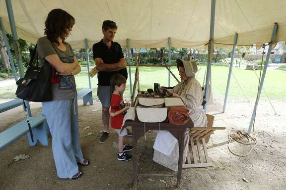 """Living historian Michelle Hill (right) talks to five-year-old Sebastian Hill (no relation) and his parents Caroline (left) and Darren - who are visiting from Perth, Australia about what life was like at the Alamo in the 1800s. Living historians like Hill are now a common site at the Shrine. The new battle of the Alamo is being fought on the airwaves and via social media, with websites and resolutions, through protests and news conferences. As demonstrators carry signs saying, """"Save the Alamo,"""" Land Commissioner George P. Bush is running campaign ads that say he's trying to do just that. After a vision of glass walls around the historic site shattered amidst protests, a proposal to move the Cenotaph is the latest rallying point for critics who say they'll work to oust Bush over the changes in the May 6 GOP primary. And they say San Antonio Mayor Ron Nirenberg also will face a political backlash. (Kin Man Hui/San Antonio Express-News)"""