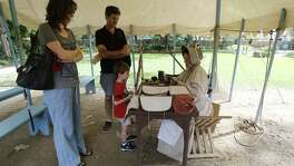 "Living historian Michelle Hill (right) talks to five-year-old Sebastian Hill (no relation) and his parents Caroline (left) and Darren - who are visiting from Perth, Australia about what life was like at the Alamo in the 1800s. Living historians like Hill are now a common site at the Shrine. The new battle of the Alamo is being fought on the airwaves and via social media, with websites and resolutions, through protests and news conferences. As demonstrators carry signs saying, ""Save the Alamo,"" Land Commissioner George P. Bush is running campaign ads that say he's trying to do just that. After a vision of glass walls around the historic site shattered amidst protests, a proposal to move the Cenotaph is the latest rallying point for critics who say they'll work to oust Bush over the changes in the May 6 GOP primary. And they say San Antonio Mayor Ron Nirenberg also will face a political backlash. (Kin Man Hui/San Antonio Express-News)"